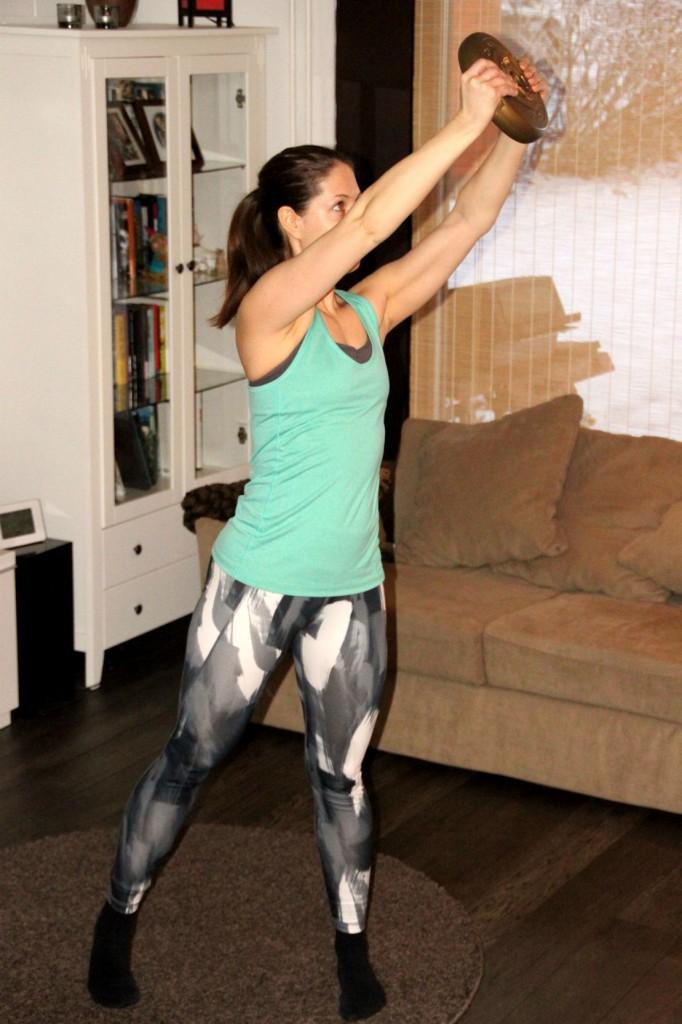 Kierrä levypaino toiselle puolelle vieden se samalla yläviistoon. Ota vauhtia myös jaloista ojentaen polvet. Tee esimerkiksi 10 toistoa, jonka jälkeen sama toiselle puolelle.