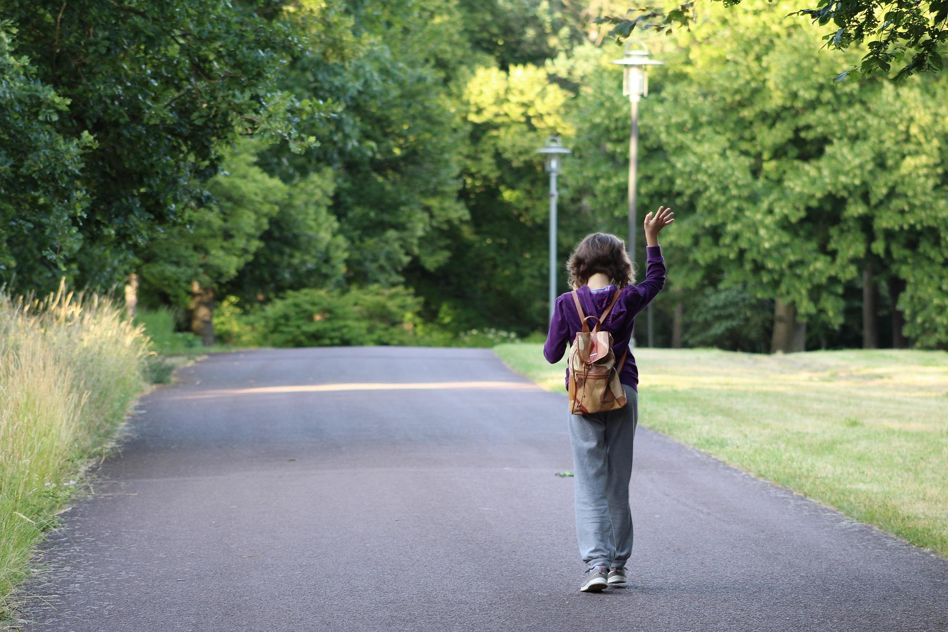 Tyttö kulkee tiellä reppu selässään ja vilkuttaa