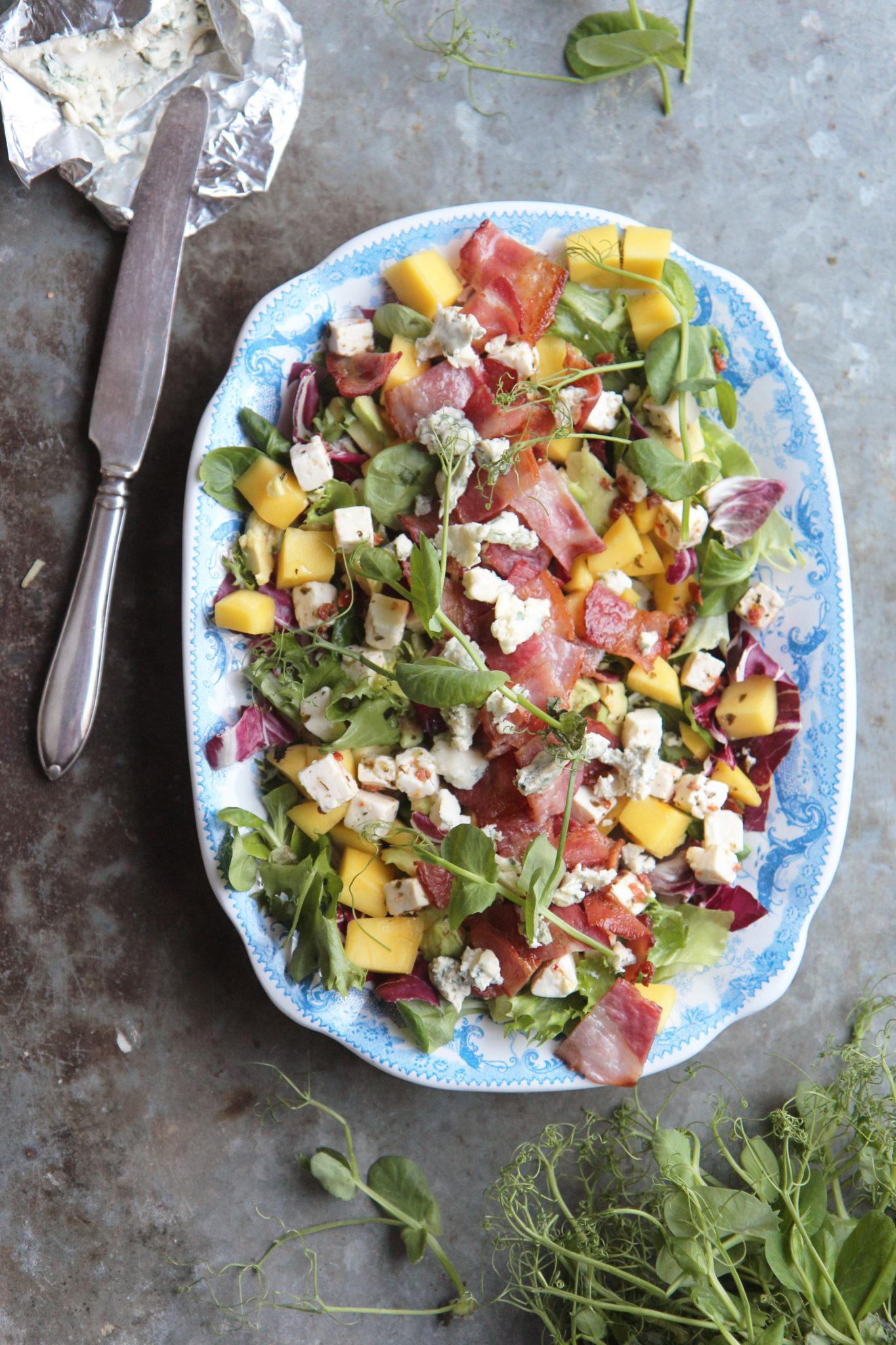 Aurinkoinen salaatti mangolla, rapealla prosciutolla sekä homejuustolla