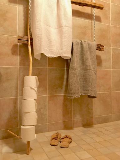 Vinkkinä vessapaperirullateline. Toinen vessamme on samassa tulassa kuin suihku. Vessapaperit on katajakepissä ja pyyhkeet kuivuvat rustiikilla telineellään