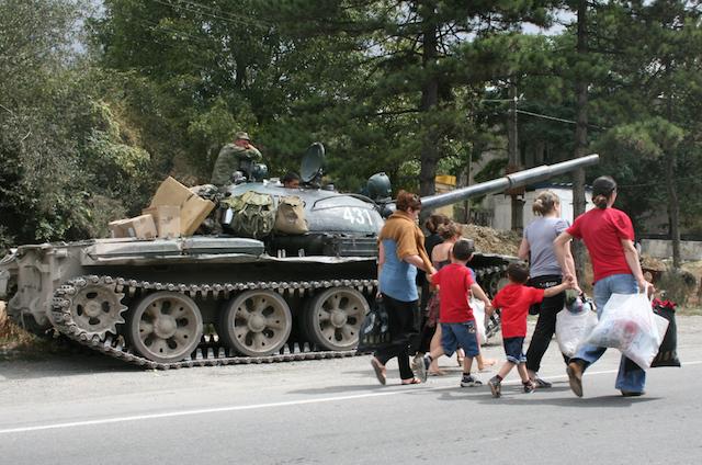 Pakolaiset Etelä-Ossetiasta  ohittavat venäläissotilaat Georgiassa vuonna 2008.